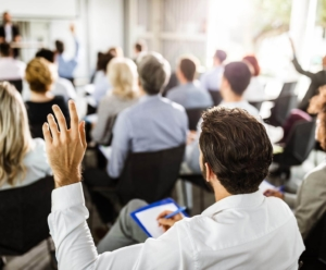 Back of man sitting in a chair raising his hand in a conference